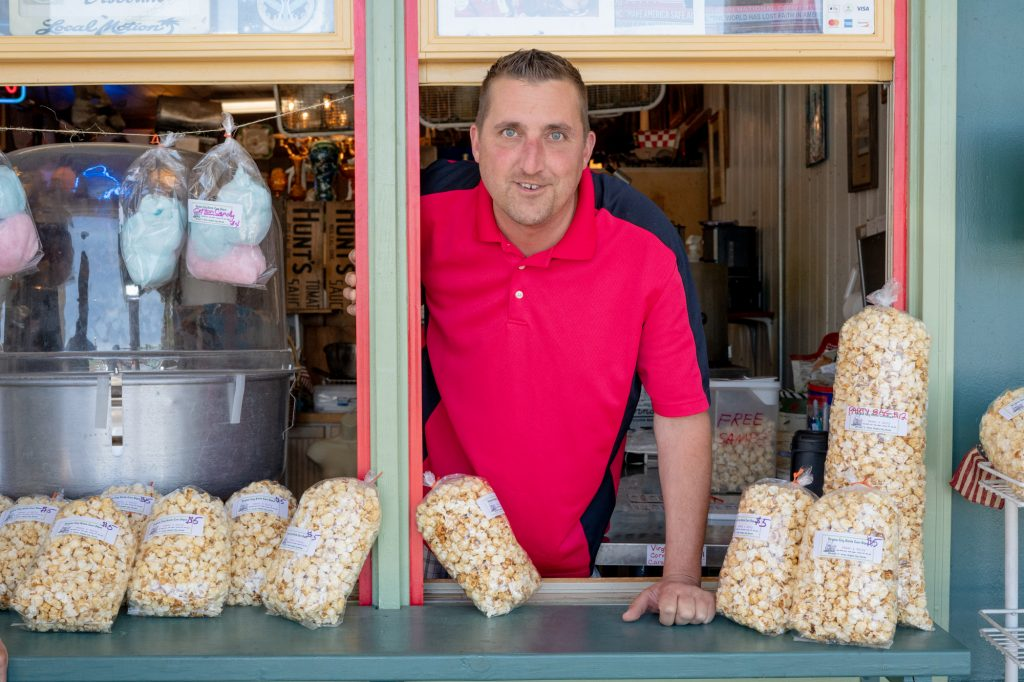 """""""I come from an ethnic family. My daughter is half African-American so I am very sensitive to the topic of hate,"""" Paul Coombes said. """"I think all races have a lot of work to do."""" Coombes handed out free samples of kettle corn to tourists outside Breck and Dave's Kettle Corn Depot on Virginia City's South C Street. (Lenny Martinez/News21)"""
