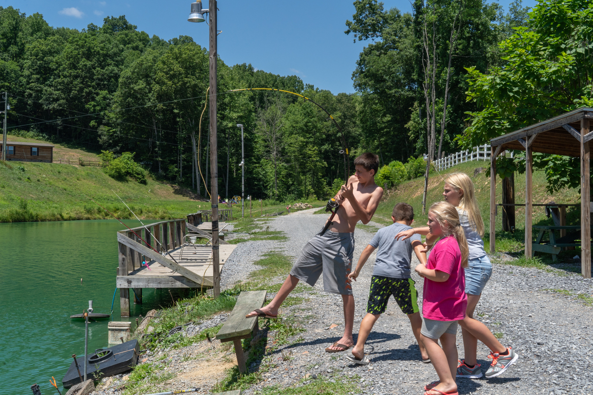 "Tristan ""Turtle"" Hylton of Beckley, West Virginia, reels in his line at Brandy's Catfish and Trout Pond while Leah J. King, Jayden Farnsworth and Uriah Farnsworth await what they hope is a big catch."