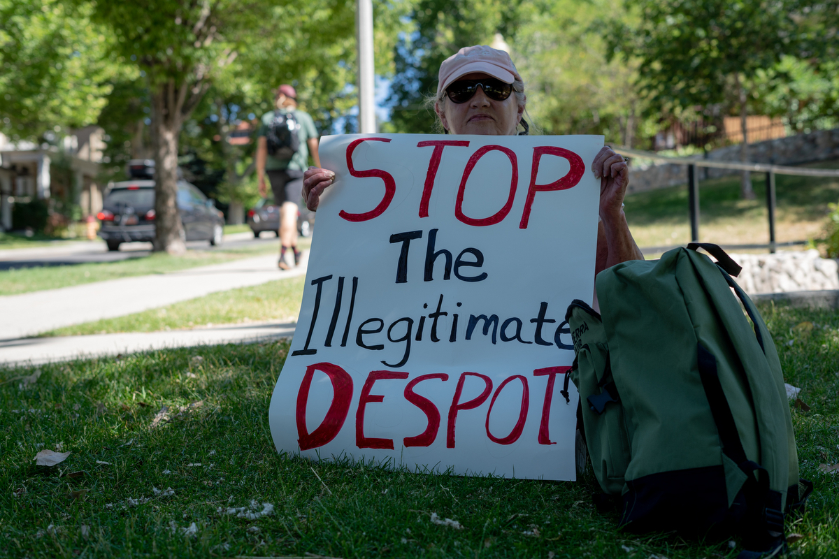 "Sitting on a hill in City Park Creek in Salt Lake City, Michelle Calwley smoked and held a sign protesting Trump as other protesters trudged up State Street to the Utah State Capitol Building. ""I think we're going backwards. Totally backwards, when a large majority of us just want to be together,"" Michelle said. (Lenny Martinez Dominguez/News21)"