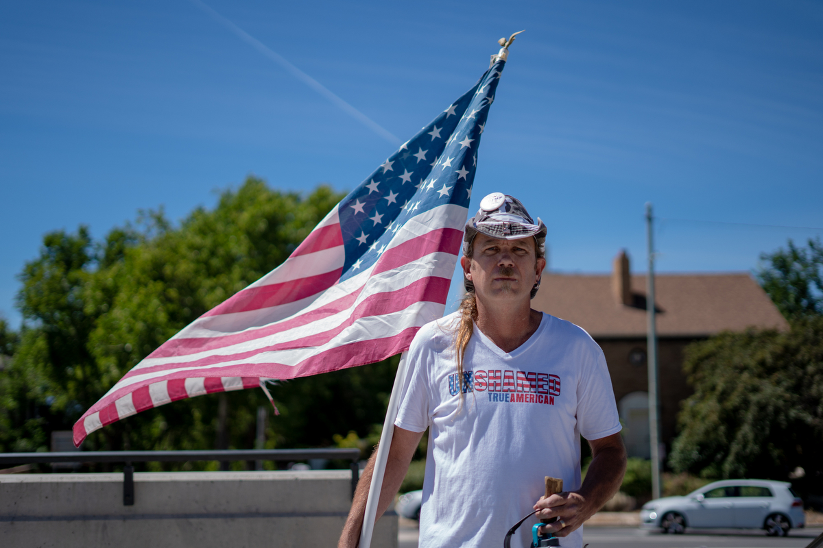 """Every race causes problems for America. There are laws to keep civil order. If we don't have civil order, our social order breaks down. So it's not just the illegal immigrants that cause a lot of problems,"" Martin Turner IV. An American flag in his hands and a Trump-Pence 2016 pin on his hat, Martin, stood quietly on the periphery of the protest at the Utah State Capitol Building. (Lenny Martinez Dominguez/News21)"