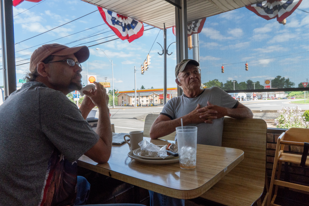 "William Bailey (right) has been visiting the Omelet Shoppe in Beckley, West Virginia, every day for the past three years. Bailey has resided in other locations, but he always comes back to the Beckley community. ""It's home. It's where I was born and raised,"" he said. Bailey described two flags that he keeps in his yard, despite one showing significant signs of age. ""My neighbor asked me why I keep that tattered thing up and I said, 'It's to remind me of eight years of Obama,'"" Bailey said. (Tilly Marlatt/News21)"