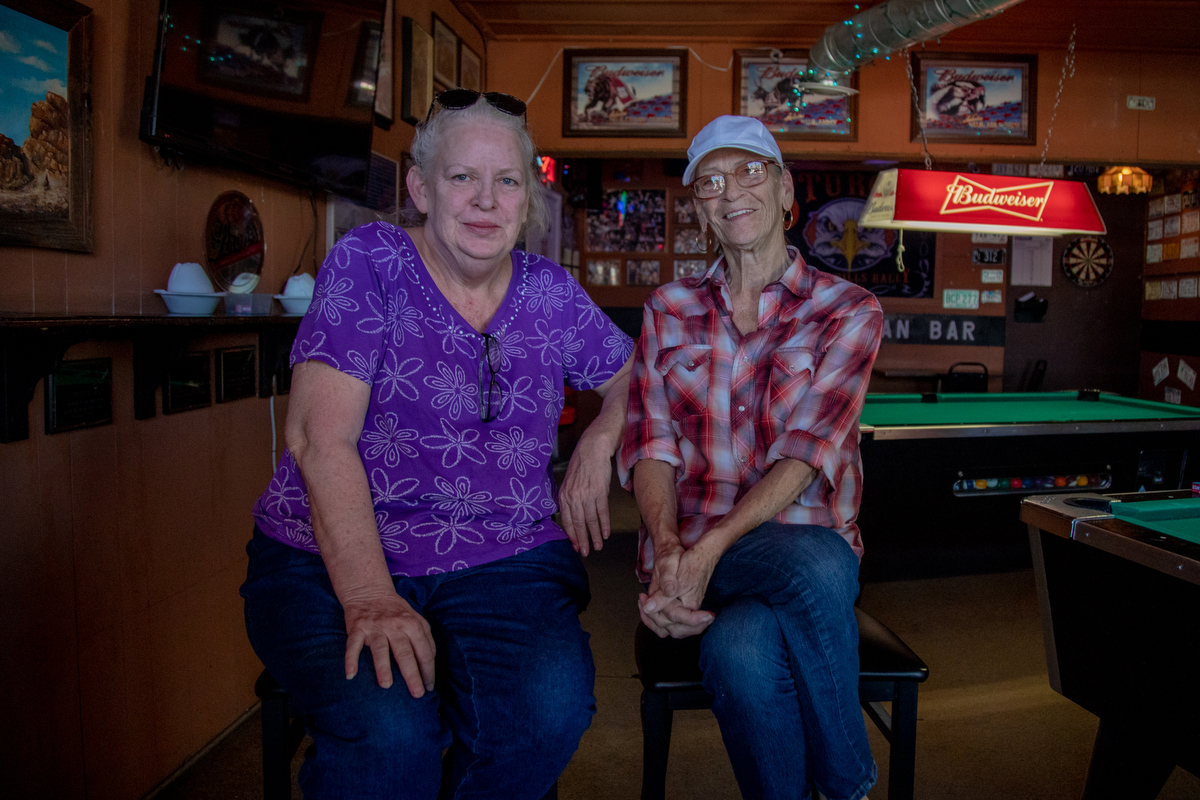 "Laurette Rogers (left) and Wedda Warrick (right) have been drinking partners for close to three years since Wedda moved to Twentynine Palms. Although hesitant to speak initially, Laurette jumped in to exclaim: ""If you were raised by bigoted parents, you're bigoted. If you're not raised by bigoted parents, you take people as they are. And that's all it's down to."" (Lenny Martinez Dominguez/News21)"