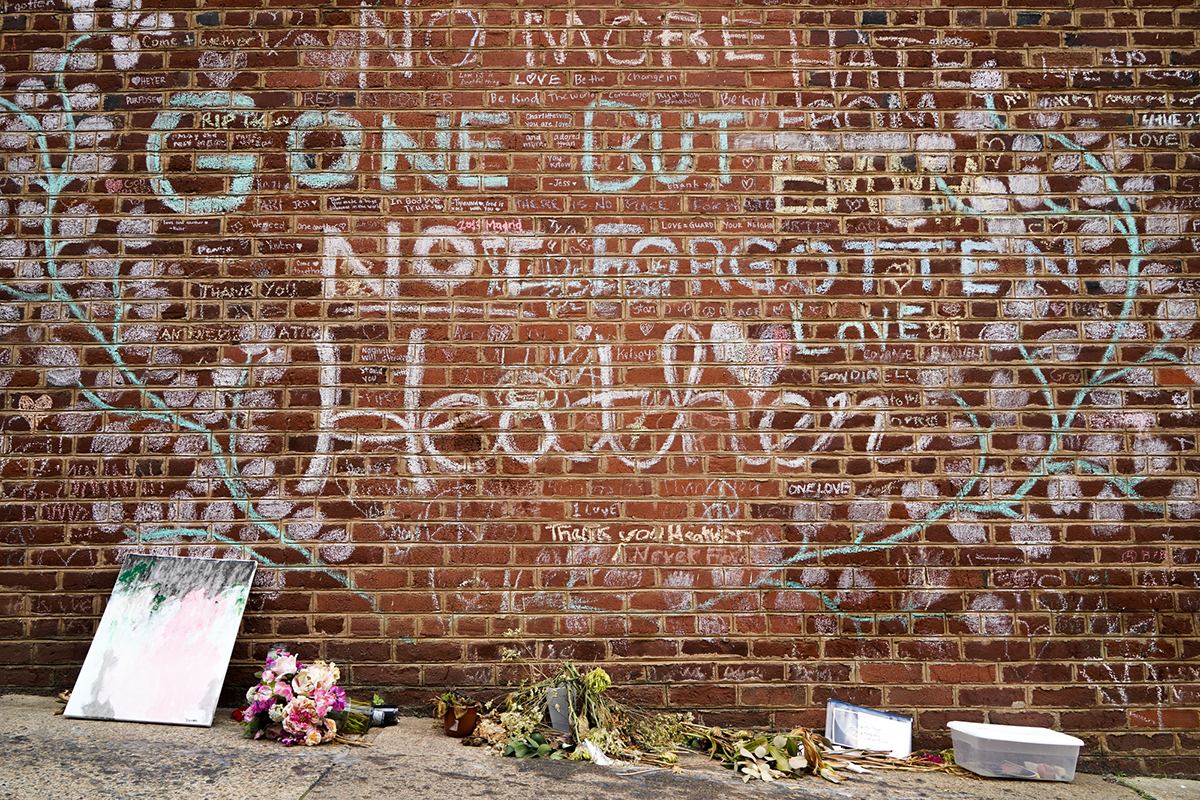 Flowers and gifts sit under the memorial wall for Heather Heyer in Charlottesville, Virginia, just off the Honorary Heather Heyer Way. The city renamed the stretch of Fourth Street for Heyer, 32, who was killed by a motorist. (Kianna Gardner/News21)
